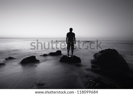 black and white seascape with alone man on the rocks