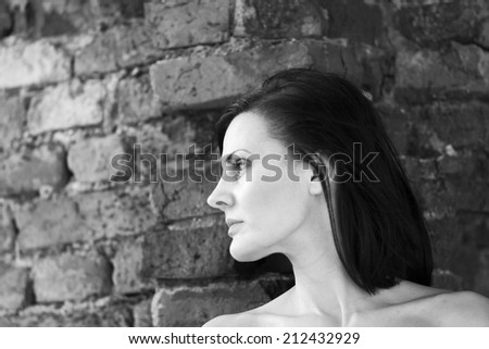 Black and white shot of a beautiful, brunette woman in an old, abandoned house looking sad and melancholic