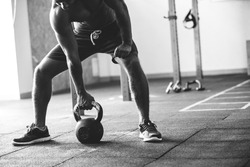 Black and white shot of an athlete with a bare torso. Athletic built man doing kettlebell exercise