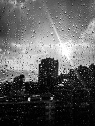 Black-and-white shot of raindrops on the glass against the city background. The sun after the rain. Monochrome