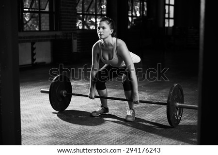 Black And White Shot Of Woman Preparing to Lift Weights