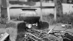Black and white shot, Outdoor Indian earthen cooking stove Countryside stove or Chulha or clay stove with a black colored circular vessel on it,