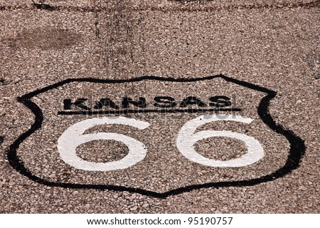 Black and white sign painted on the road for Route 66 in Kansas