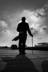 Black and white silhouette of an elegant gentleman on a rooftop with a cane, wearing a long a coattail and a bowler hat