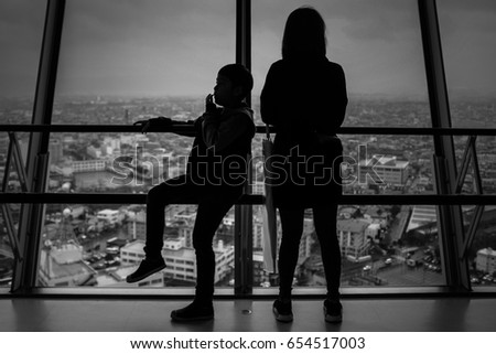 Black and white silhouette of Mum and Son with the city background. #654517003