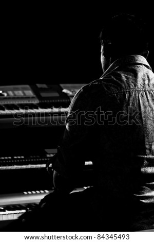Black and white silhouette portrait of a keyboard player playing 3 keyboards.
