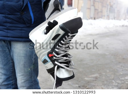 black and white skates in the hands for skating on the ice in winter and figure skating, the theme of sports and recreation  #1310122993