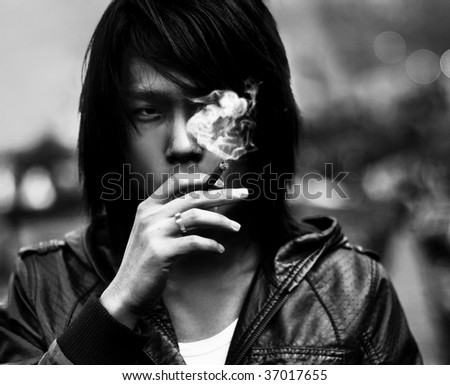 Black and white smoking asian man portrat - stock photo