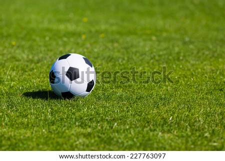 Black and white soccer ball on green soccer pitch.
