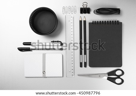 Black and white stationery on gray desk: notepads, pencils, scissors, stapler, clip, pins, ruler, pens, pen pot. Top view point.