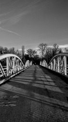 Black and white steel bridge road. Monochrome artistic photography. Shadows at sundown. Structure shilouette. Straight line themed image. Urban architecture landscape picture. Abstract creative photo.