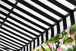 black and white striped awning with green garden.
