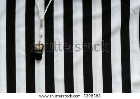 black and white striped referee jersey with a whistle to the left, copy space on the right hand side of image