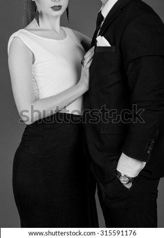 black and white Studio photos erotic young couple on black background. Girl in a dress, man in a business suit
