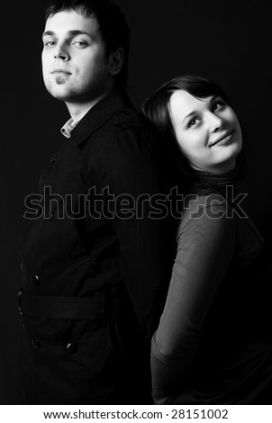 black and white studio portrait of a serious man and a dreamy young woman standing back to back