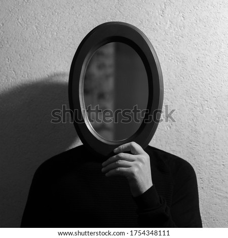 Black and white studio portrait of young man holding oval mirror on face. Background of textured wall. Photo stock ©