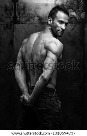 black and white studio shot of strong athletic man on dark grunge background