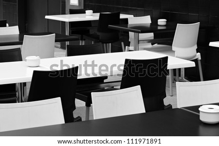 Black and white tables and chairs. A street small cafe.