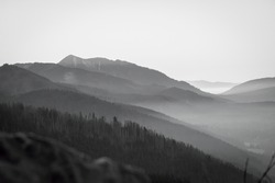 Black and white Tatra Mountain view. Fog is covering the valley, clear sky is illuminating the ridge of the hills. Selective focus on the peak, blurred background.