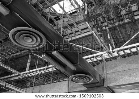 Black and white tone, low angle interior view of open ceiling of old abandon factory or industrial building which show beam truss structure, AC conduct system and hanging chains. #1509102503