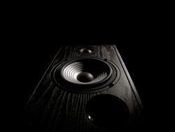 black and white toned image of an audio speaker isolated on a black background