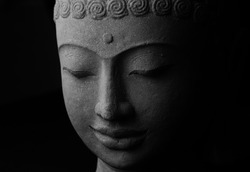 Black and white top view closeup picture of Buddha statue. Buddha's face