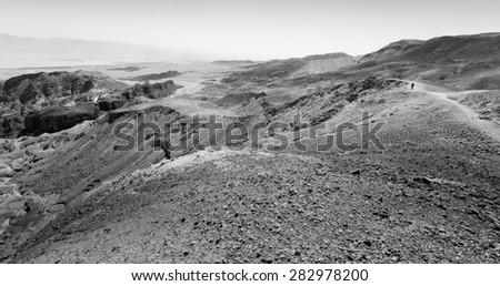 Black and white tourist backpacker traveling walking desert mountain cliffs, Arava, negev desert, Israel.