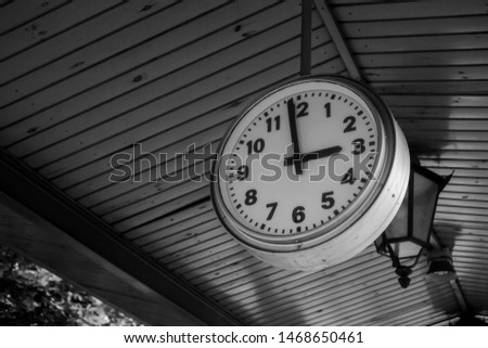 Black and white train station clock showing one minute before 3:00, 3 PM - three PM, three o'clock. Waiting for a train or other transport, time passing and arriving on time or being late concept  #1468650461