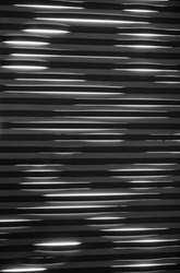Black and White Venetian Blind Backdrop.  Shade and sunlight against metal blinds for a monochrome photo  background.