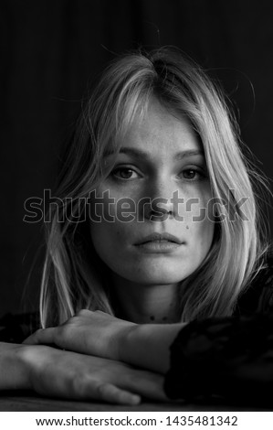 black and white vertical close up headshot of blond woman in studio with melancholic expression on sad face with black background and natural light