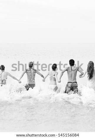 Black and white view of a group of five mixed friends holding hands and running into the sea water together, being spontaneous and having fun while on a summer vacation on a beach.