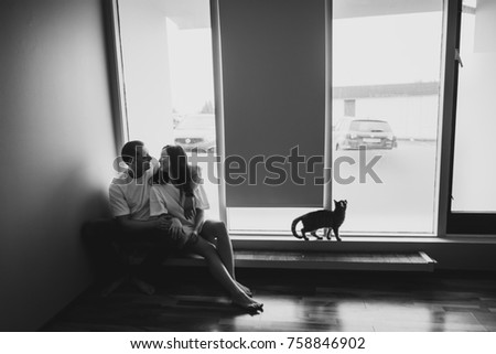 Black and white View of beautiful young loving couple close to the big window at home. They are sitting on windowsill, embracing and looking to each other. Small cute cat walk close on the windowsill.