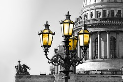 Black and white view of Saint Isaac Cathedral in Saint Petersburg with color vintage street lamp with yellow light