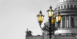 Black and white view of Saint Petersburg with vintage street lamp with yellow light. Saint Isaac Cathedral in retro tone. Black and white photo with color