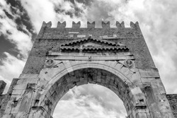Black and white view of the Arch of Augustus in Rimini, Italy, the oldest extant Roman arch, against a dramatic sky