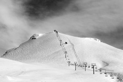 Black and white view on ski slope and chair-lift at sun winter morning. Caucasus Mountains. Georgia, region Gudauri, Mt. Kudebi.