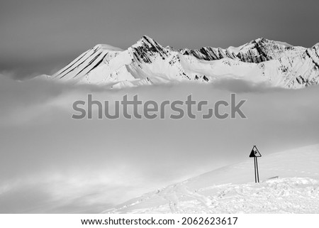 Black and white view on warning sing on ski slope and snowy mountains in fog. Caucasus Mountains at winter, Georgia, region Gudauri.