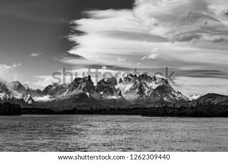 Black and white vintage photograph of the Torres del Paine massif with the Cuernos del Paine in the foreground and a dramatic sky, Patagonia, Chile.