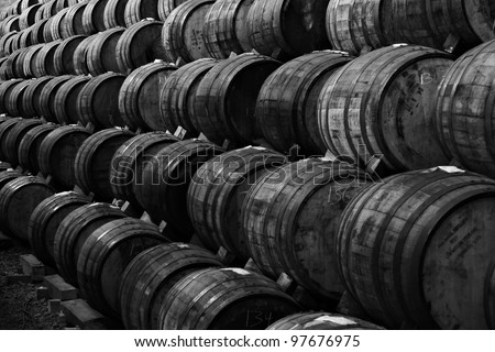 Black and white Wine barrels stacked in the old cellar of the winery.