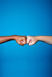 Black and white women hands showing each other friendship and respect on blue background - Isolated diverse multiethnic female hands supporting - brotherhood, racism, equality concept