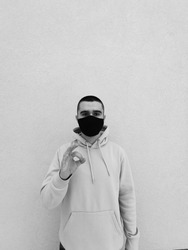 Black and White Young caucasian short haired male wearing blue sweatshirt and black mask while standing in front of isolated beige wall, showing okay sign, decent experience.