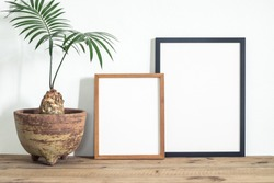 Black and wooden brown frame poster with beautiful houseplant on wooden table. Home decoration