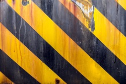 Black and yellow caution strips line painted on metal surface, rusty grunge background