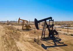 Black and yellow oil pumps. Pumpjack. Oil industry equipment. Daylight, morning, blue sky. USA