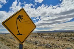black and yellow road sign of a palm tree leaning over in strong wind.Vast open landscape in Patagonia