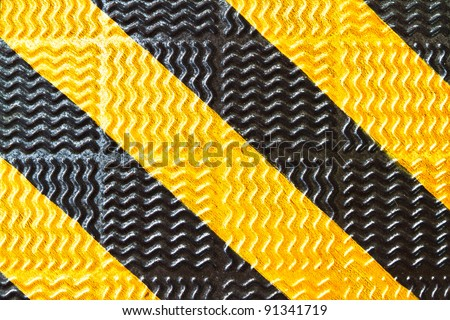 black and yellow strip on steel walkway