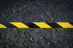Black and yellow striped tapes on dark background. Restricted area border. Passage is forbidden.