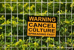 Black and yellow warning sign on a fence stating