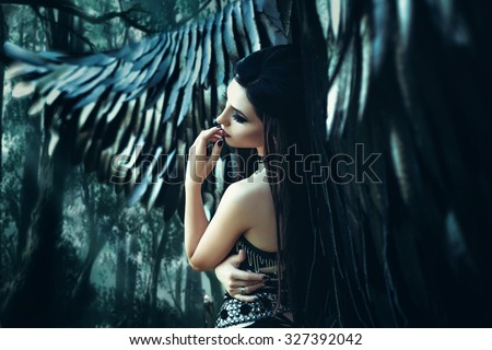 Stock Photo Black Angel. Pretty girl-demon with black wings. An image for Halloween. Image of an old book of fairy tales. Fashionable toning with noise