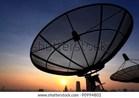black antenna communication satellite dish over sunset sky in cityscape